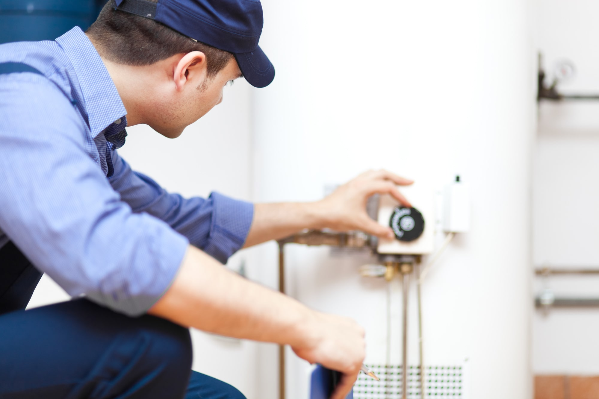 A plumber inspecting and maintaining a hot water tank in Edmonton